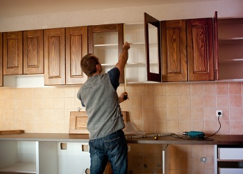 Man installing kitchen cabinets for Kitchen Remodeling in Peoria IL